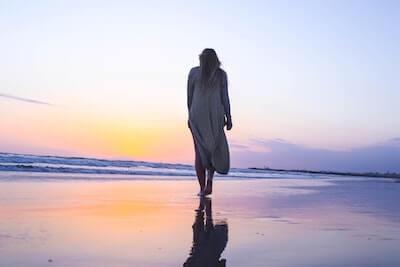 波打ち際を歩く女性