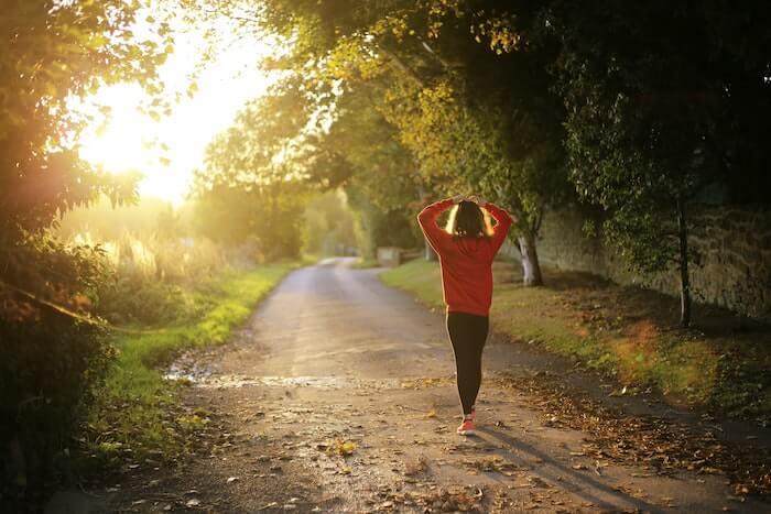 朝日の中を歩く女性